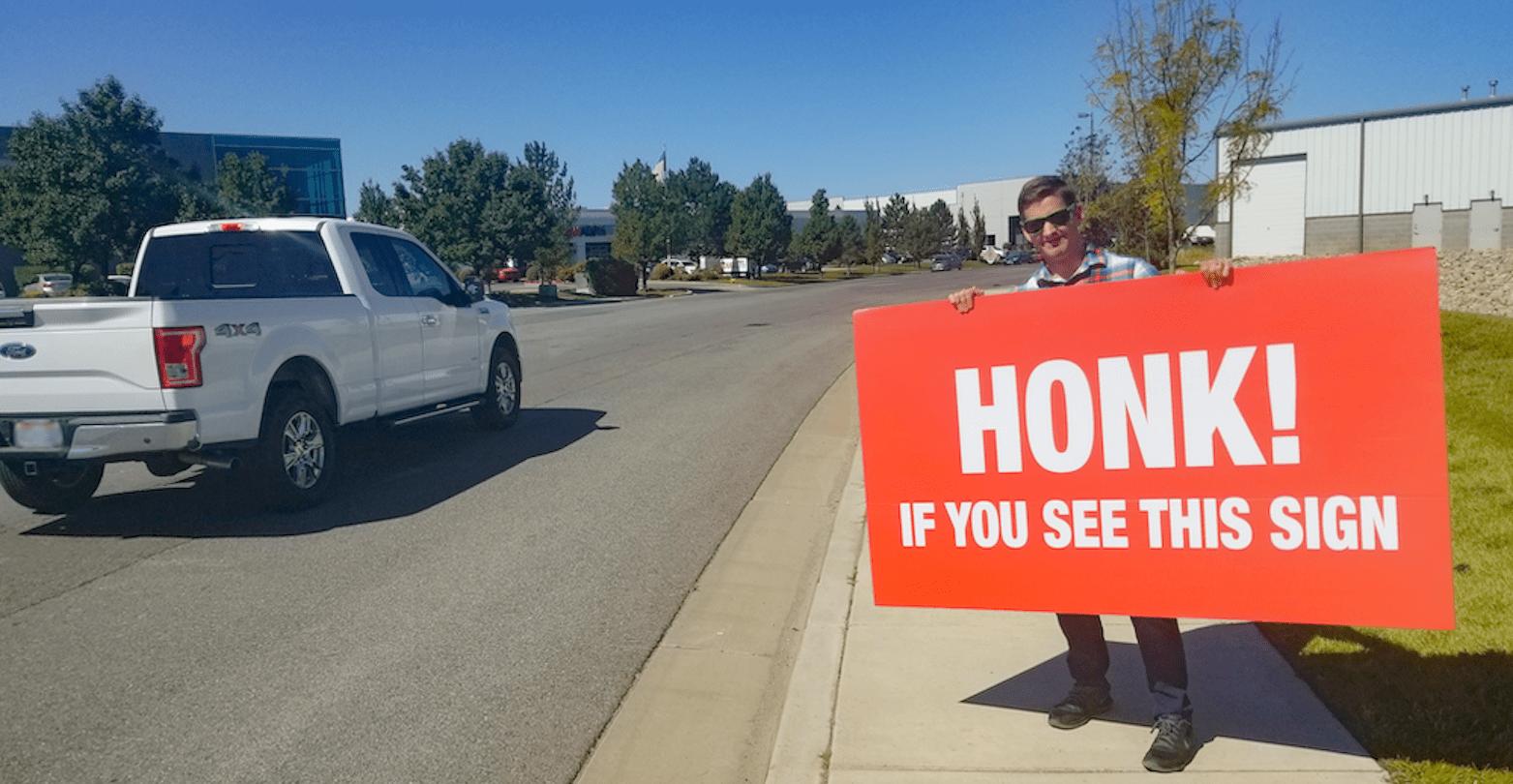 Man holding sign on roadside.
