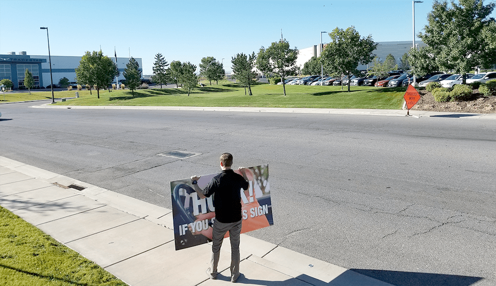 Image of man holding sign with empty street.