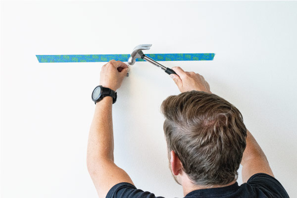 Hammering in nail & hook to wall