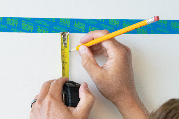 Marking a point on a wall using painters tape and tape measure as a guide.