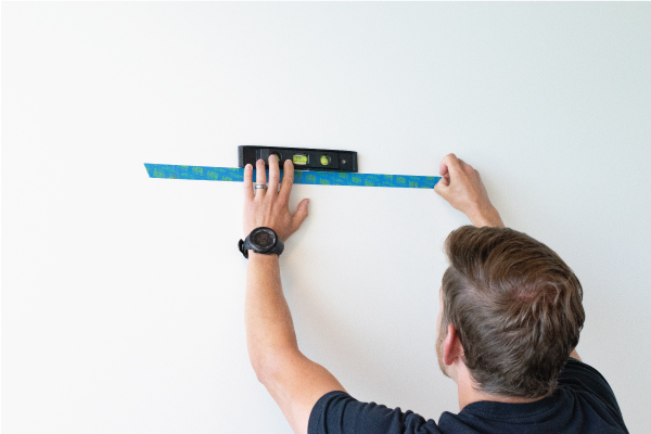 Person placing tape on wall using a spirit level to align it.