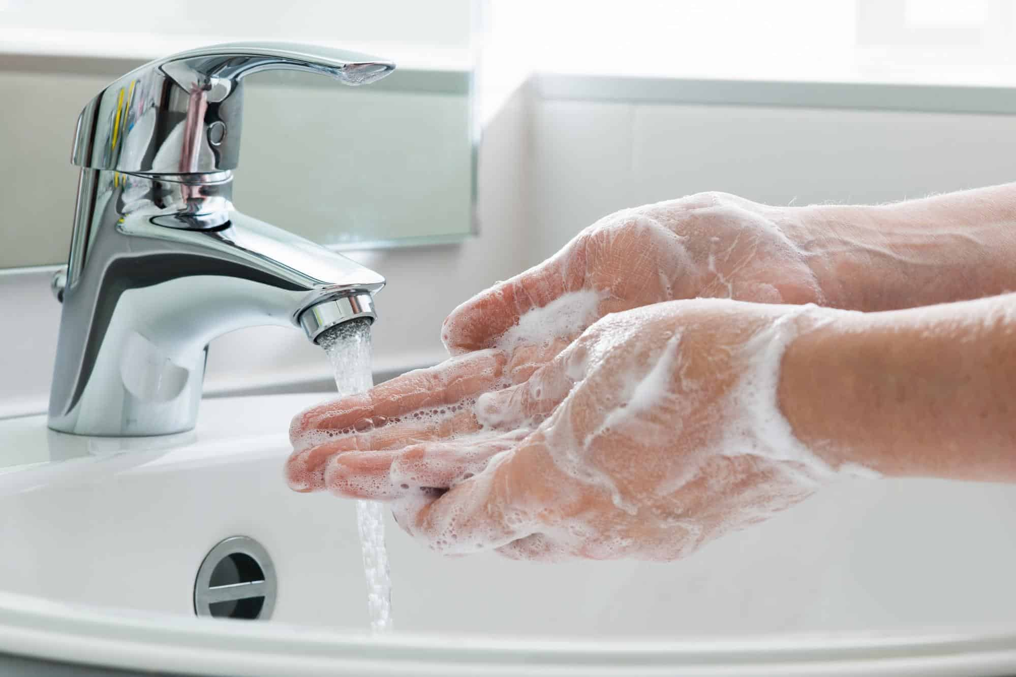 Washing hands with soap and water at bathroom sink