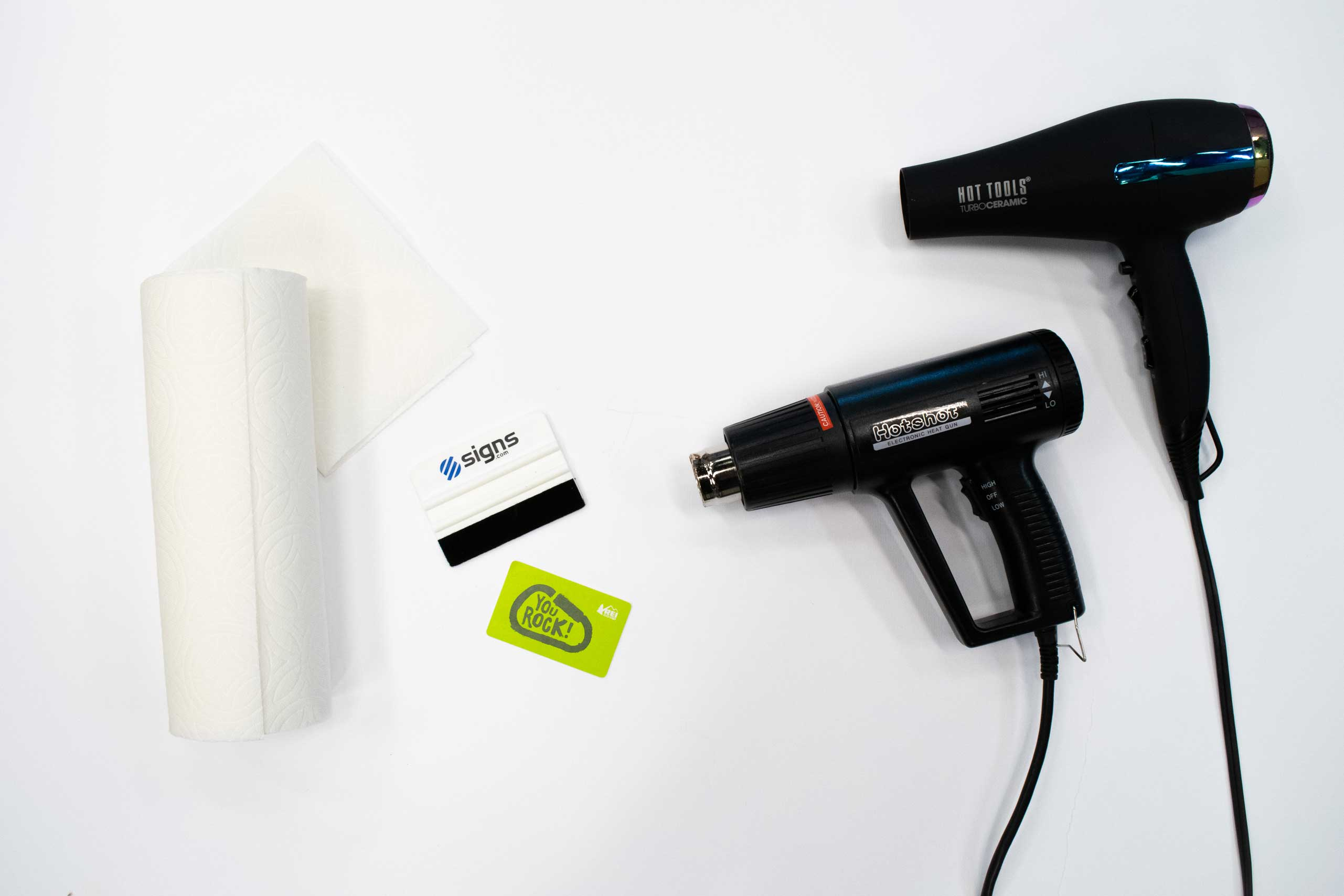Supplies for removing vinyl lettering, including paper towels, plastic chisel/credit card, and heat gun/blow dryer