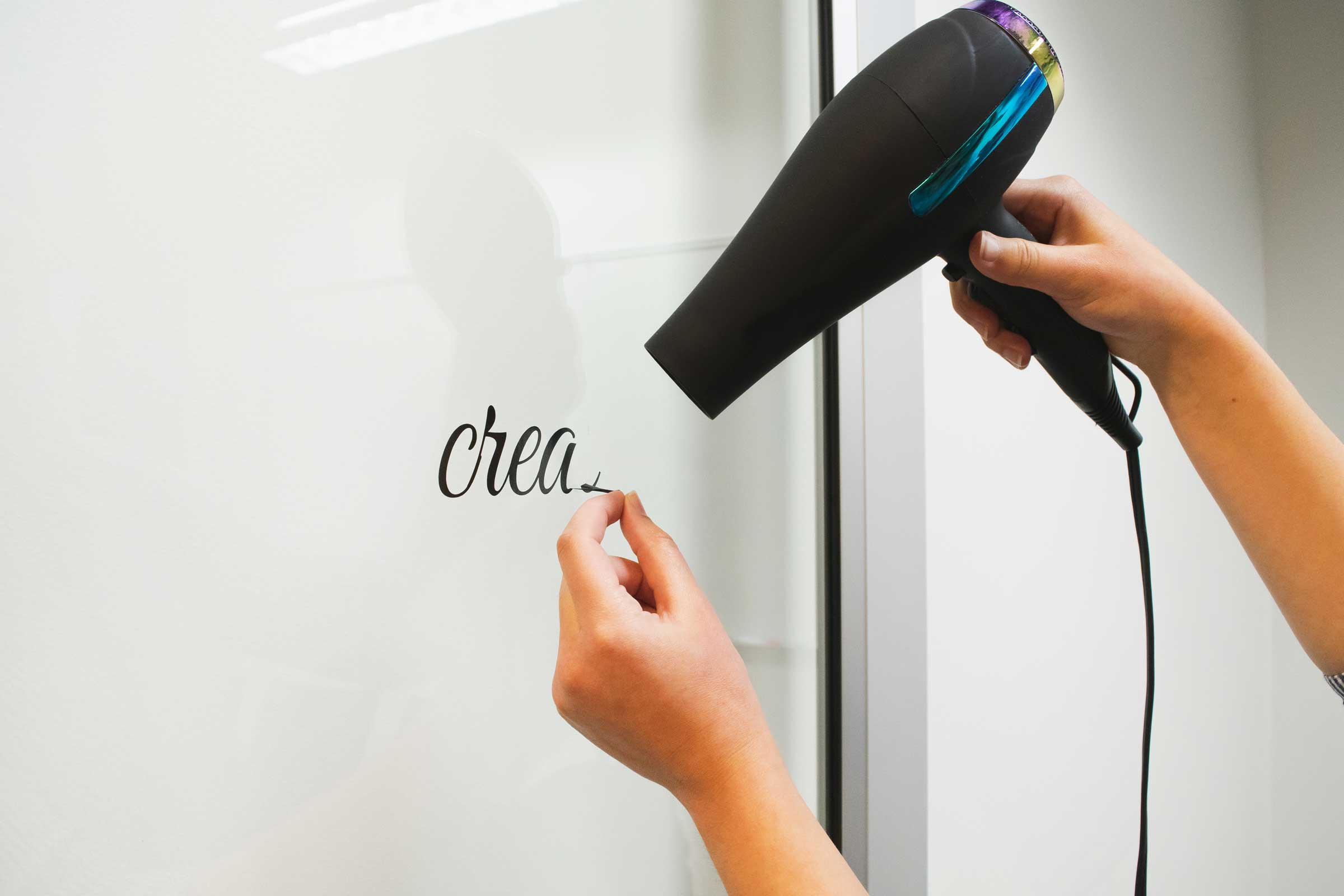 Using a blow dryer to remove hard-to-remove vinyl lettering