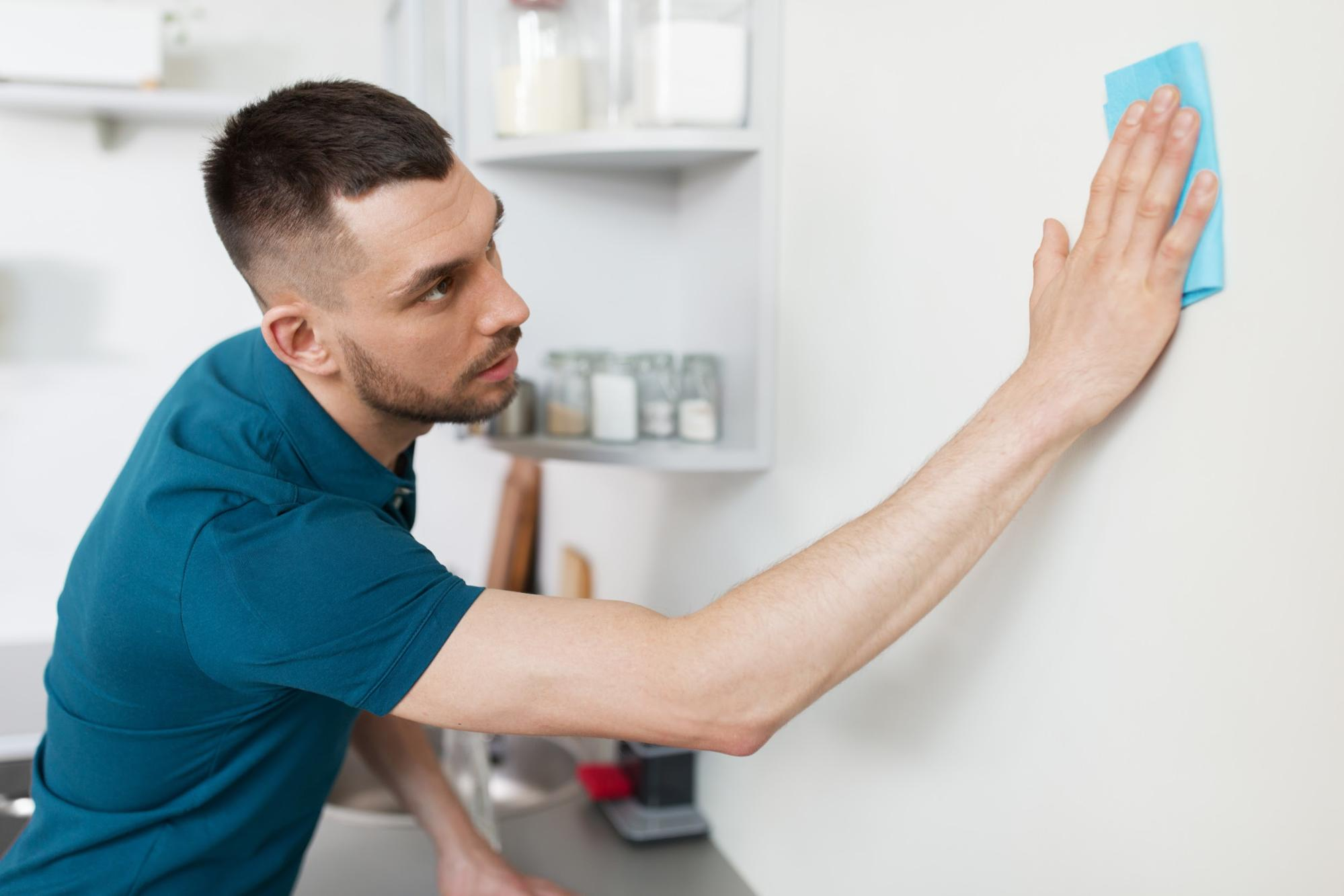 Man cleaning wall in home kitchen with blue microfiber cloth