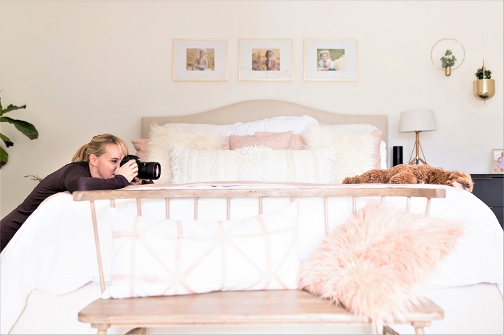 Jen Frase taking a photo of a dog lying on a bed