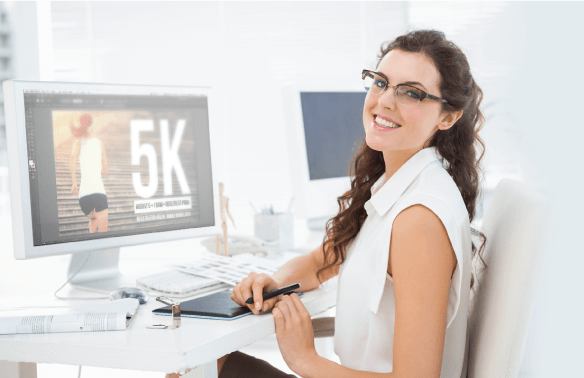 Woman smiling at a desk with computer monitor displaying design editing software